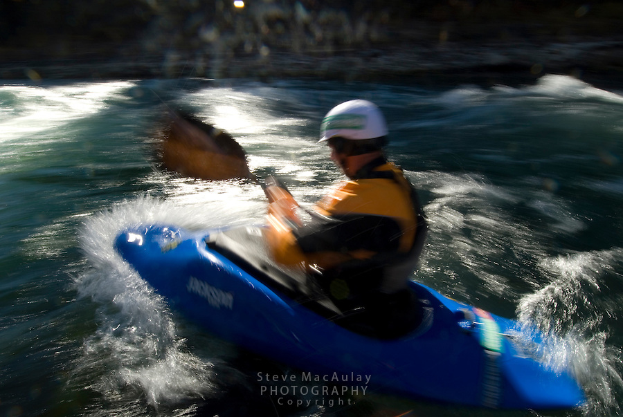 Motion blur shot of whitewater kayaker in yellow paddle jacket, white helmet and blue kayak, Snake River, Jackson,  Wyoming.
