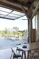The wall of the barn hinges to give views of the terrace and creating an open-air dining area