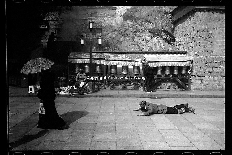 A Tibetan pilgrim prostrates outside the Potala Palace in Lhasa, Tibet,  September 2016.
