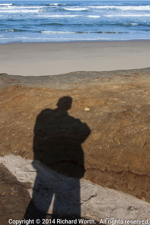 A beach visitor's shadow on a sandstone outcropping with sandy beach and ocean waves in the background.