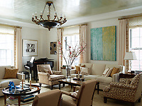 In the living room, a luminous glow is cast onto the Venetian plaster walls by the aluminium-leaf ceiling. The custom-made sofa is covered in a Kravet chenille, the armchairs are upholstered in a Rogers & Goffigon fabric and the club chairs are in a leopard print by Tafford Fabrics. The 1940s cocktail table is attributed to Jacques Quinet.