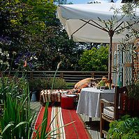 A sun-drenched terrace complete with shady garden umbrella and small dining table overlooking the mill pond