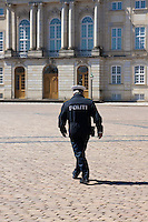 Policeman in Copenhagen, Denmark walking across the square at Amalienborg Palace.