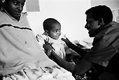 Asmara, Eritrea.November 2002.Birhan Aim Hospital  (Light to the Eye Hospital)..2 year old Filmon was blind when he entered the hospital. Both of his eyes were operated. His father ( right) and mother (left) enjoy their child?s sight for the first time.