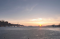 Evening view at sunset over an ice covered Riddarfjarden water towards the west with Soder, the southern part of Stockholm to the left and Kungsholmen to the right Stockholm, Sweden, Sverige, Europe