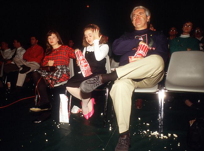 "Smyrna, Ga.: Rep. Newt Gingrich (R-Ga.) eats popcorn during a screening of the movie ""Boystown"" in Smyrna, Ga. on Dec. 30, 1994."