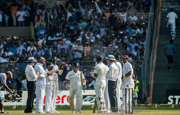 West Indies players welcome Sachin Tendulkar onto the pitch as he comes out to bat during his 200th (and last) test cricket match before his retirement at Wankhede Stadium in Mumbai.
