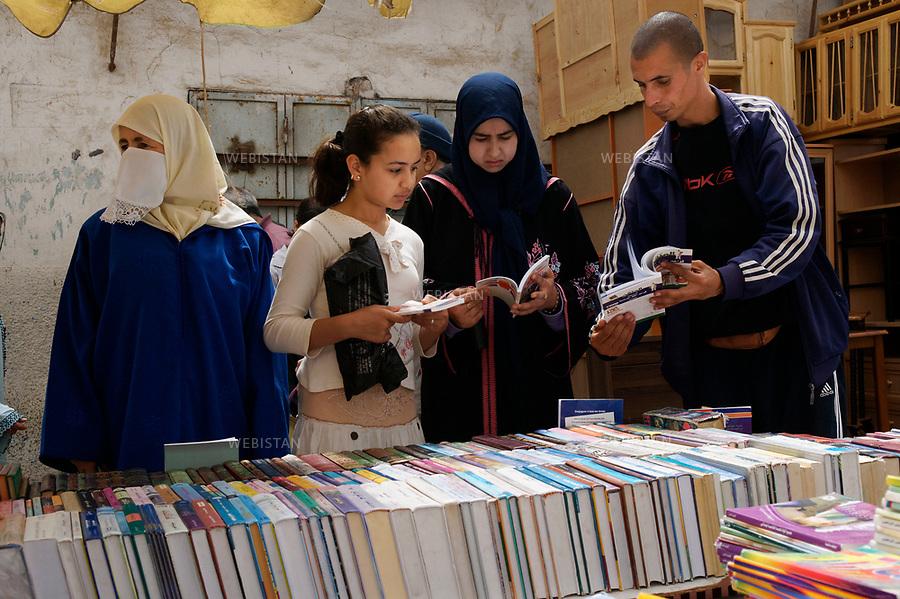 Algerie. Oran. 09 Avril 2011.Un commercant renseigne des clientes vetues d'une djelaba, d'un foulard et d'une voilette (&laquo; aajar &raquo;) devant un stand de livres au marche &laquo; Madina Jadida &raquo; (&laquo; la nouvelle ville &raquo;).<br /><br /><br />Algeria, Oran. April 9th 2011<br />A retailer talks to the client dressed in djellaba, a headscarf and a veil  (&quot;aajar&quot;) infront of a book stand at the market &quot;Madina Jadida&quot;(&quot;the new city&quot;).