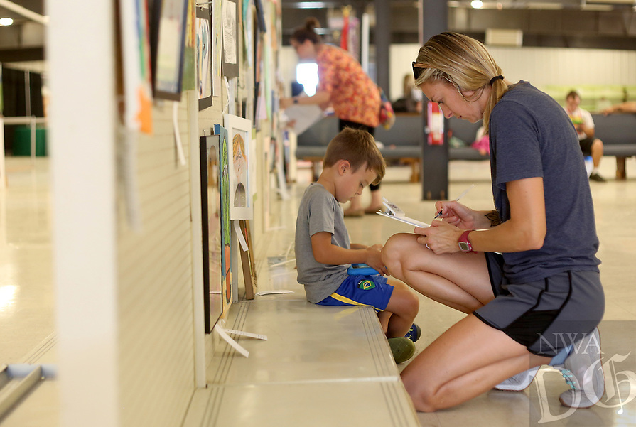 NWA Democrat-Gazette/DAVID GOTTSCHALK Hayes Brener, 4, sits with his mother Nakia Tuesday, August 7, 2018, as she judges the Kids 7-12 art division inside the Exhibition Hall at the 2018 Benton County Fair in Bentonville. The 2018 Benton County Fair runs through Saturday, August 11, and features amusement rides, arts displays, a horse show, goat yoga and other exhibits and activities.