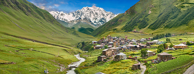 Stone medieval Svaneti tower houses of Chvibiani with mount Shkhara (5193m) behind, Ushguli, Upper Svaneti, Samegrelo-Zemo Svaneti, Mestia, Georgia.  Chvibiani is a group of four remote villages. At 2,200 m (7217 ft) above sea level in the Caucasus mountains these are the highest inhabited villages in Europe. Chvibiani has well preserved stone Svanetian defensive tower houses attached to stone family houses. Mount Shkhara is the highest mountain in the Caucasus range.  A UNESCO World Heritage Site.