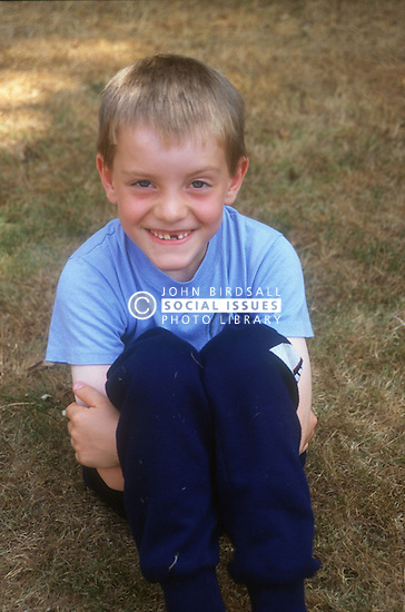 Portrait of young boy with missing teeth sitting on grass in park smiling,
