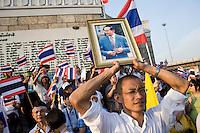 Des manifestants pro-gouvernementaux portent l'image du roi Bumibhol sur la place de la Victoire pendant une manifestation Chemises jaunes contre la r&eacute;volte des Chemises rouges qui occupent Bangkok en ce mois d'avril 2010. L'image intouchable du roi est instrumentalis&eacute;e de part et d'autre, les chemises jaunes accusant les rouges de mettre en p&eacute;ril la monarchie.<br /> <br /> <br /> Eng:<br /> A man is hanging a portrait of the king Bumibol, while Pro-government supporters are demonstrating at the Victory monument in Bangkok, sunday afternoon  April 25, after the failure of negociations.