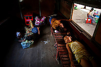 People sleep inside a circular train stopped at the Yangon's central station September 17, 2012. Around Yangon, with its growing and increasingly demanding population of almost five million, a circular train operates moving passengers through its suburbs. On a three hour long ride, a train made of rusted vehicles marked with different classes but little difference between them, takes passengers around the city stopping briefly on numerous small stations.    REUTERS/Damir Sagolj (MYANMAR)