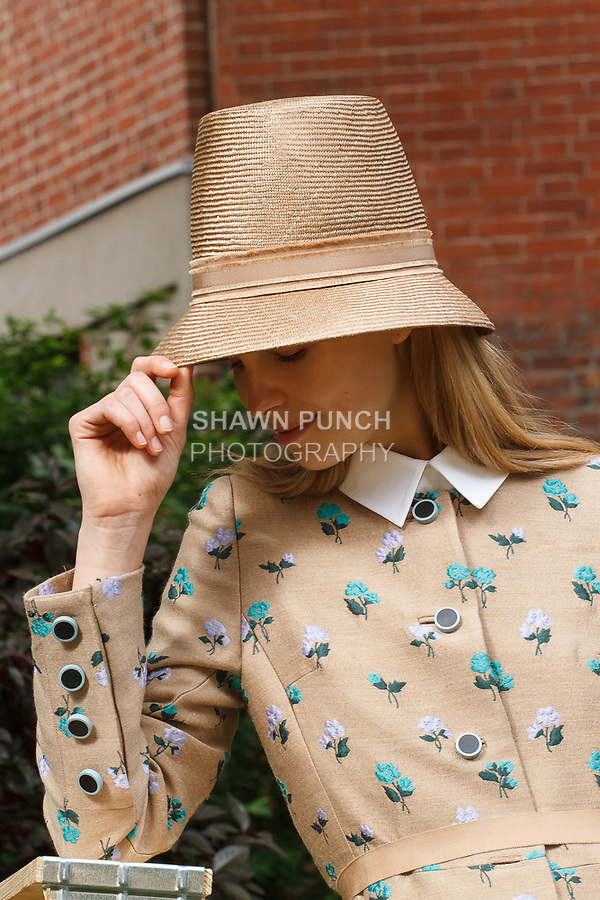 "Model poses in an outfit by Lela Rose and Rocha Millinery hat by Rosael Torres Davis, for the Lela Rose Resort 2018 ""Garden Party"" collection presentation in Jefferson Market Garden on June 7 2017, during Resort Fashion Week in New York City."