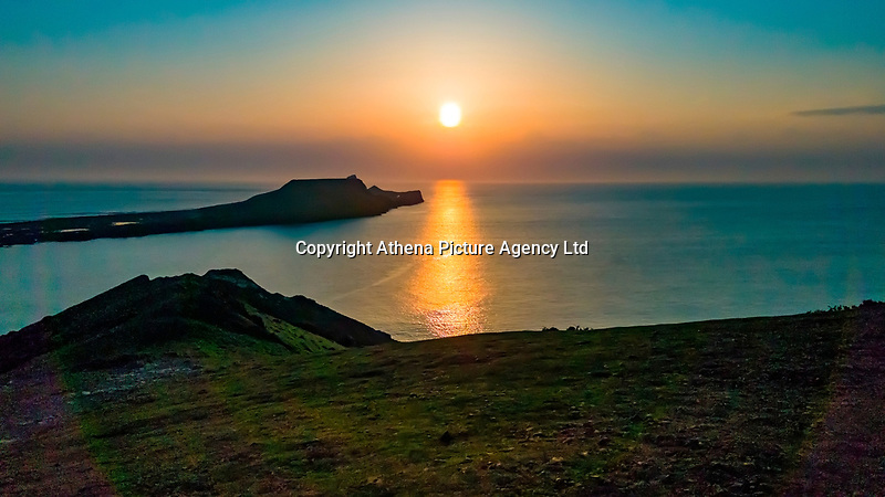 WEATHER PICTURE WALES<br /> The sun sets over Worms Head at the end of a warm sunny day in Rhossili, Gower Peninsula, Wales, UK.