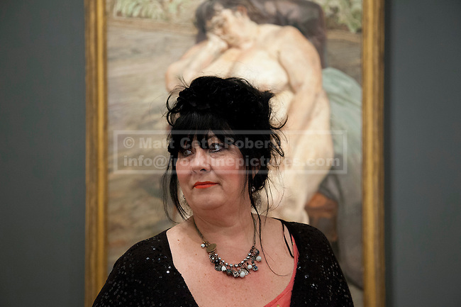 08/02/2012. LONDON, UK.  Sue Tilly poses in front of Lucian Frued's 'Sleeping by the Lion Carpet' a portrait of her on display at the National Portrait Gallery. The exhibition entitled Lucian Frued Portraits, due to open on the 9th of February 2012, represents one of the largest collections the late artists work ever assembled with over 100 paintings, drawings and etchings on display. Photo credit: Matt Cetti-Roberts