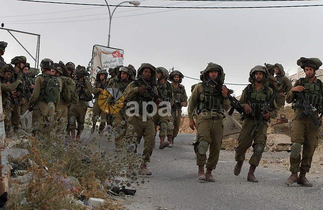 Israeli troops patrol a street during a search operation for three Israeli teenagers believed kidnapped by Palestinian militants on June 21,2014 in the town of Halhul near the West Bank city of Hebron. Israeli Prime Minister Benjamin Netanyahu has used the search to promote two other objectives ó a new crackdown on Hamas and an attempt to discredit the Palestinian unity government formed earlier this month by Western-backed President Mahmoud Abbas, which is supported by Hamas. The Islamic militant Hamas group has praised the abduction of the teenagers but has not claimed responsibility for it. Photo by Mamoun Wazwaz