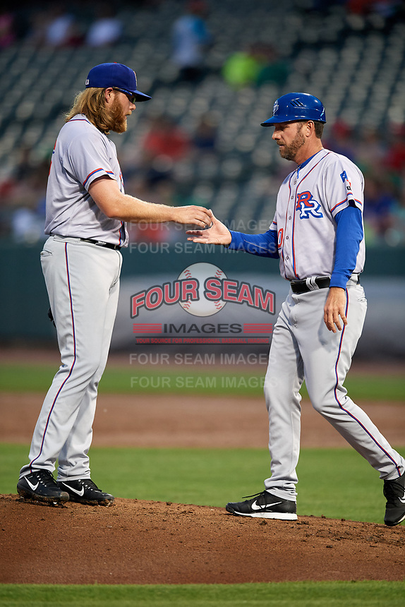 Round Rock Express manager Jason Wood (40) takes the ball from starting pitcher A.J. Griffin (56) after making a pitching change during a game against the Memphis Redbirds on April 28, 2017 at AutoZone Park in Memphis, Tennessee.  Memphis defeated Round Rock 9-1.  (Mike Janes/Four Seam Images)