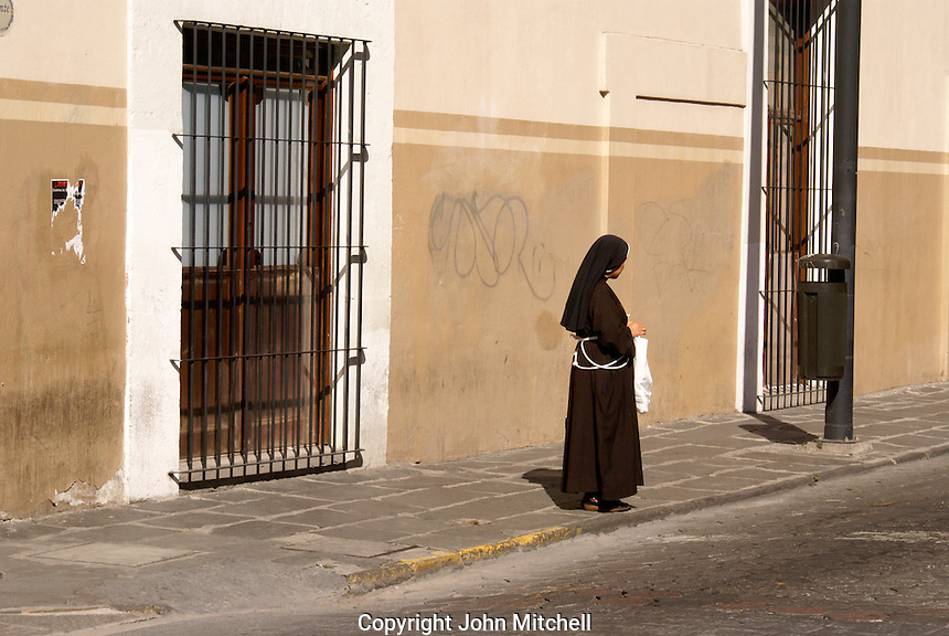 Nun standing on a street corner in the city of Puebla, Mexico. The historical center of Puebla is a UNESCO World Heritage Site..