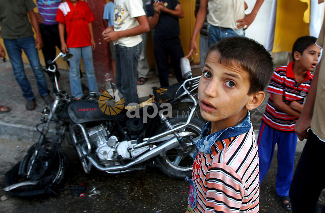Palestinians inspect a motorcycle damaged in an Israeli air strike in Deir al-Balah in the central Gaza Strip on August 24, 2011. An Israeli strike killed Ismael al-Ismar, 34, in Rafah scarcely 48 hours after militant factions had agreed to a temporary ceasefire -- on condition Israel also stopped its air strikes. Photo by Ashraf Amra