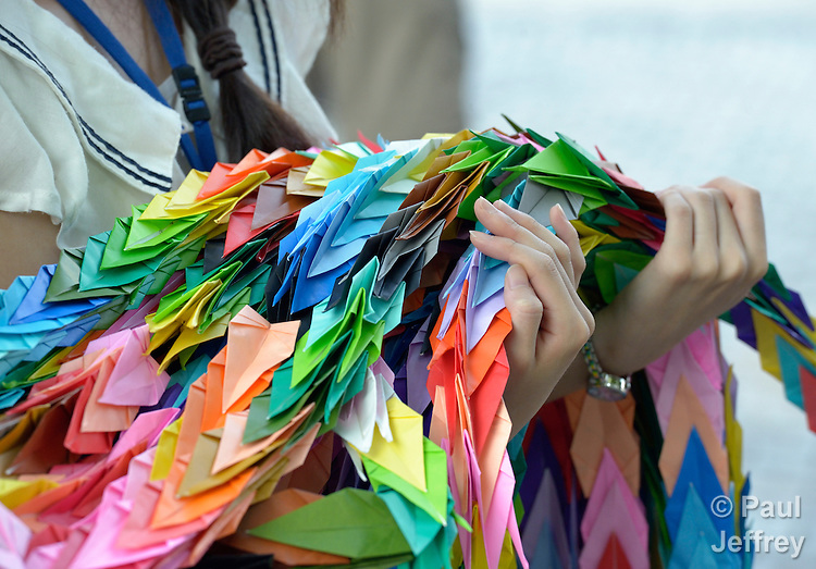 A Japanese girl carries folded paper cranes she has brought to Hiroshima in commemoration of the 70th anniversary of the U.S. dropping an atomic bomb on the Japanese city of Hiroshima. The cranes are a sign of hope and peace.