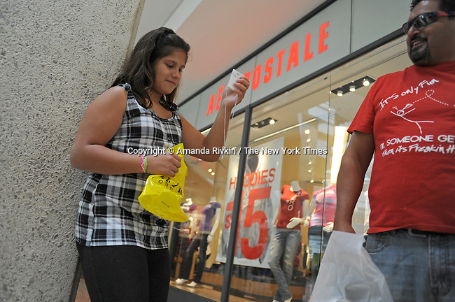 (R-L) Edison Onate, 48, of Chicago, Illinois with his daughter Alexis Onate, 12, of Bloomington, Illinois holding up a necklace her father just bought for her at Forever 21 at the Woodfield Mall in Schaumburg, Illinois on September 5, 2010.