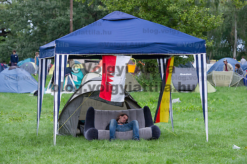 Participant sleeps under a tent with a flag on Sziget festival held in Budapest, Hungary on August 07, 2011. ATTILA VOLGYI
