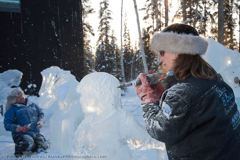 "Heather Brice, USA, carves on the multi block sculpture titled ""Guardian Angel of Mischief"" for the 2009 World Ice Art Championships in Fairbanks, Alaska. Team members: Heather Brice, Kevin Gregory, Jeff Stahl, Steve Cox"
