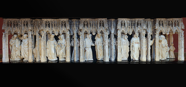 Statues of weepers under Gothic canopies under effigy of Margaret of Bavaria, from the tomb of Jean sans Peur, or John the Fearless, 1371-1419, (Jean de Valois or John of Valois, Jean I, duc de Bourgogne, or John I, Duke of Burgundy) and his wife Marguerite de Baviere, or Margaret of Bavaria, 1363- 1423, 1443-70, by Jean de la Huerta, 1413-62, and Antoine le Moiturier, 1425-97, in the Grande Salle du Palais des ducs de Bourgogne, or Salle des Gardes, a 15th century Flamboyant Gothic hall, in the Musee des Beaux-Arts de Dijon, opened 1787 in the Palace of the Dukes of Burgundy in Dijon, Burgundy, France. The tomb consists of painted alabaster effigies with lions and angels, and below, figures of pleurants or weepers among Gothic tracery. The tomb was begun in 1443 (24 years after his death), by Jean de La Huerta, and Antoine le Moiturier after 1456, and finally installed in 1470. The tombs were originally from the Chartreuse de Champmol, or Chartreuse de la Sainte-Trinite de Champmol, a Carthusian monastery which was sacked in the French Revolution and the tombs moved to Dijon cathedral then here in 1827. Picture by Manuel Cohen