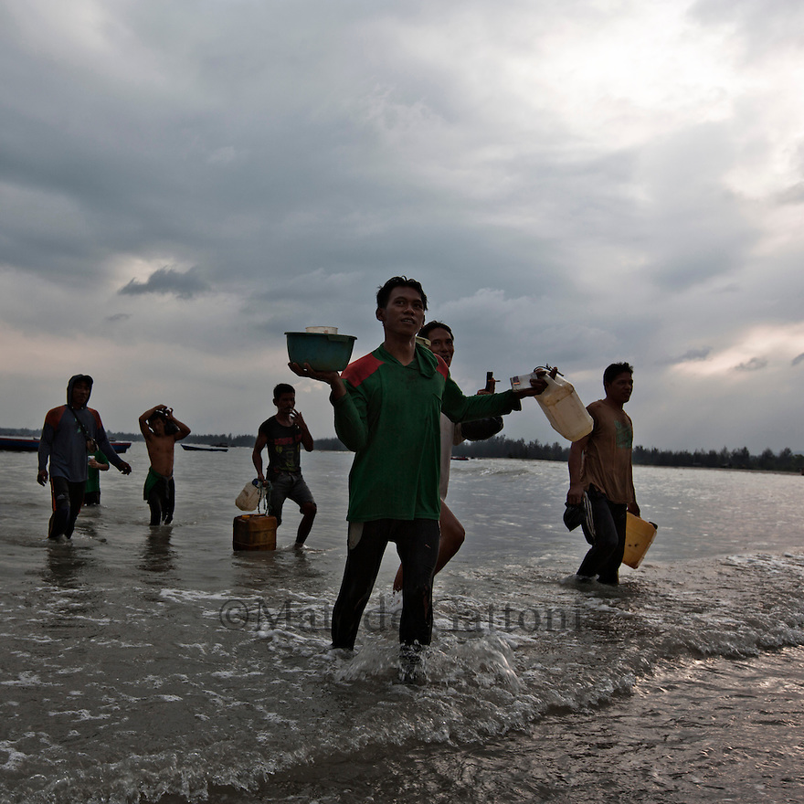 Indonesia - Bangka Island - Rebo -Young men coming back from offshore mining at sundown. Each pontoon can collect around 15 kg of low concentrate tin per day. Depending on the tin global price, at the end of the day each miner can earn around 15 USD, double the average pay of a farm labourer.