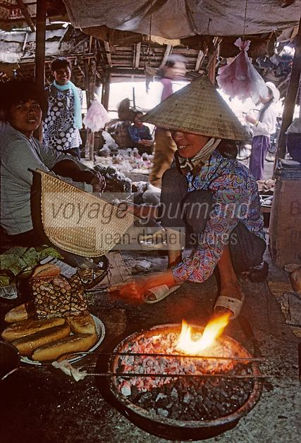 Asie/Vietnam/Baie d'Halong: Femme faisant la cuisine sur du charbon de bois dans un petit marché