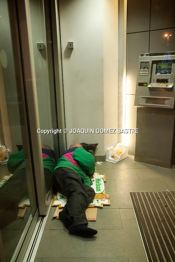A homeless person sleeping in an ATM in Santander (Spain), and this is very often on the streets of the cities due to the crisis..photo © JOAQUIN GOMEZ SASTRE