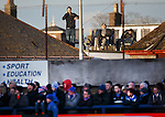 A trio of fans with deck chairs and beers watching the game from on the top of the roof of a house at Links Park