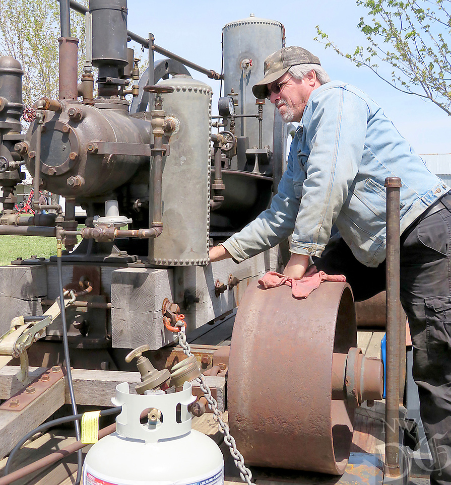 Westside Eagle Observer/RANDY MOLL<br /> Tired Iron of the Ozarks will hold its 27th annual Spring Crankup from 8 a.m. to 5 p.m. on Friday and Saturday, April 19 and 20, at the club's showgrounds, located at 13344 Taylor Orchard Road, in Gentry. The event will feature a parade of power at noon each day, hit and miss engines, a log cabin and outhouse, a working blacksmith shop and sawmills, rope making, home furnishings and lots of antique tractors, equipment and tools. This year's spring show will give special attention to garden tractors and Waterloo engines. A silent auction will be held Friday through Saturday at 3 p.m. Admission to the show and parking are free. In the photo above, Bryan Parsons of Springdale works to start an 1886 Farrar and Trefts oilfield steam engine at the Tired Iron of the Ozarks show in Gentry on April 20, 2018.