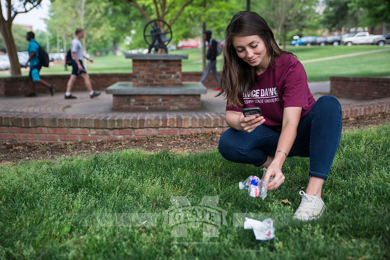 Daisy Grant, a graduate student in biological sciences from Biloxi, picks up trash and takes a photo of it as part of the #Take2Miss and #MaroonGoesGreen social media challenge. As part of MSU's Earth Week activities, participants are asked to find two pieces of litter today [April 18] and to post one picture of those items on Facebook or Instagram using the hashtags #Take2Miss and #MaroonGoesGreen. Mississippi State is competing against the University of Mississippi, Millsaps College, Delta State University and Hinds Community College, who all are collecting litter throughout the day as well.<br />  (photo by Sarah Dutton / &copy; Mississippi State University)