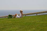 Woman with Straw Hat Gazing Out to Sea on Summer's Day on Block Island