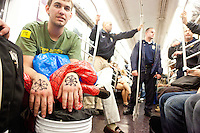 "After clashing together in Times Square protester Andrew Stevens,  with ""Occupy Wall Street"", and the NYPD amicably ride the subway together downtown on October 15, 2011 in New York City.  While crowd estimates numbered in the tens of thousands, police tactics (including nets, motor scooters, barricades, arrests, and intimidation by riders on horseback) prevented the crowd, which had been split up, from joining together as one in the middle of Times Square."