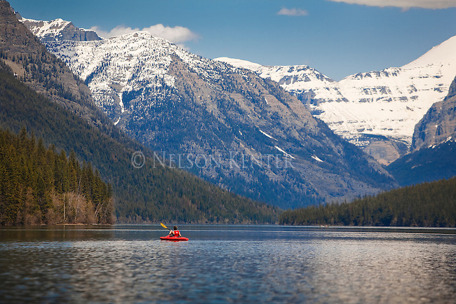 A red kayak on Bowman Lake in Glacier National Park with snow capped mountain peaks at the head of the lake