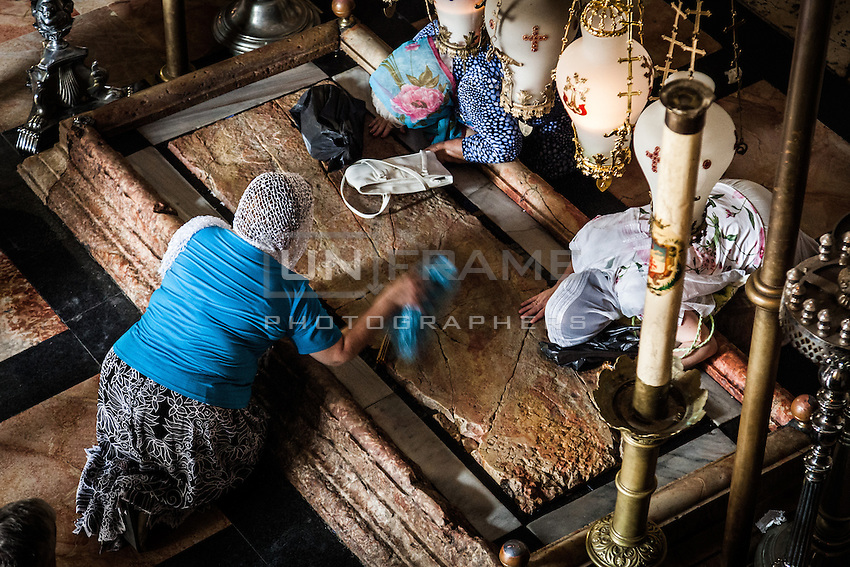 Worshippers praying and kissing the Stone of Anointing,  also known as The Stone of Unction. East Jerusalem