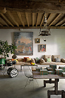 A casual living area features a concrete banquette along one wall lined with cushions and an antique drum kit