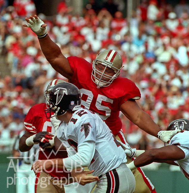 San Francisco 49ers vs. Atlanta Falcons at Candlestick Park Sunday, October 18, 1992.  49ers Beat Falcons 56-17.  San Francisco 49ers nose tackle Michael Carter (95) blocks passing lane for Atlanta Falcons quarterback Chris Miller (12).