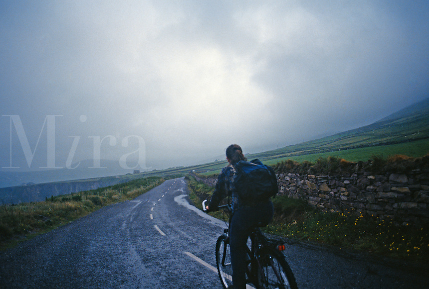 .Man riding bike on a deserted contry road, County Galway, Ireland