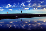 With a bright blue sky above - and reflected in the storm drain below - a beachgoer makes her way along Venice Beach (at Rose Ave.), late Tuesday afternoon in Venice.