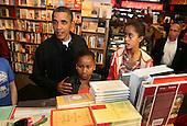 United States President Barack Obama, left, and daughters Sasha, center, and Malia, right, shop for books in the Kramerbooks book store in Washington, Saturday, November 26, 2011..Credit: Martin Simon / Pool via CNP