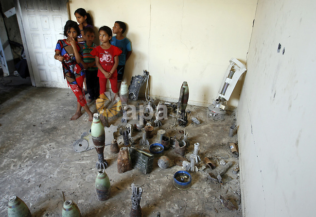 """Palestinian children look at mortars and spent ammunition that, Suleiman Abu Jamaa, 35, collected around his destroyed home in Khan Yunis in the southern Gaza Strip on September 11, 2014. Israel's deputy foreign minister,Tzahi Hanegbi , warned that Hamas was likely to resume """"violence"""" if it feels it has made no political gains from upcoming talks in Cairo. Photo by Abed Rahim Khatib"""