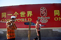 "Local Uihgur pass a ""One World One Dream"" slogan of the Beijing Olympic Games in Kashgar, China. An attack happened in Kashgar yesterday killed 16 police.."