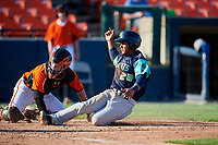 Lynchburg Hillcats catcher Angel Lopez Alvarez (20) slides home safely as catcher Stuart Levy (18) can not come up with the throw during the first game of a doubleheader against the Frederick Keys on June 12, 2018 at Nymeo Field at Harry Grove Stadium in Frederick, Maryland.  Frederick defeated Lynchburg 2-1.  (Mike Janes/Four Seam Images)