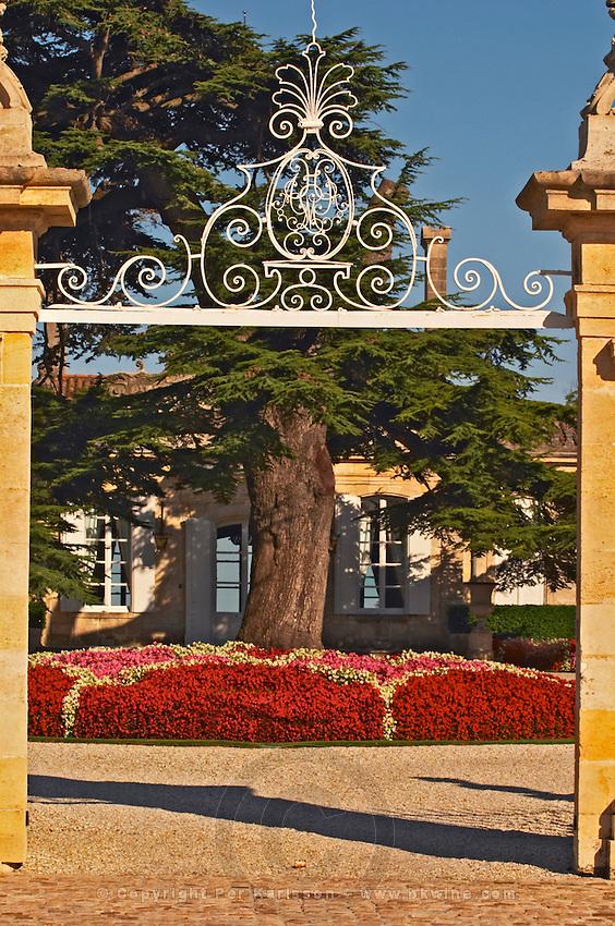 The entrance gate to Chateau Beychevelle in Saint Julien. Beautiful flower arrangements and huge cedar tree