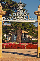 The entrance gate to Chateau Beychevelle in Saint Julien. Beautiful flower arrangements and huge cedar tree