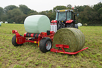 Wrapping a bale of silage in plastic in a field, Cheshire.